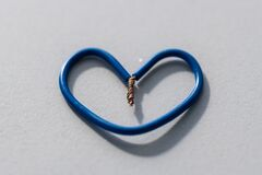 A small  heart made from blue cables on a gray background