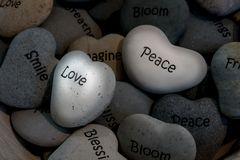 Inspirational heart shaped stones in basket. Small heart shaped gray stones with inspirational mantras such as peace smile blessing love bloom friend breathe royalty free stock photos