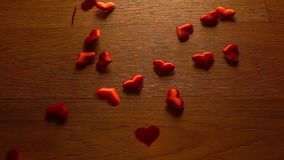 Small hearts combine big heart shape on wooden surface. Super slow motion video stock video
