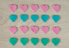 Small hearts of pink and blue color lie on a white wooden table royalty free stock photography