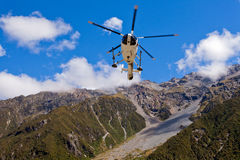 Rescue helicopter fly over mountainous wilderness Stock Photography