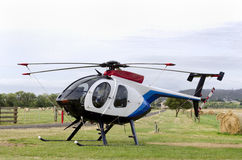 Small helicopter in paddock with hay-bales Royalty Free Stock Photo