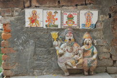 Small Hindu wall shrine in Kathmandu, Nepal. This is a small Hindu shrine on a brick wall in Kathmandu, Nepal, with statues and pictures of gods royalty free stock photos