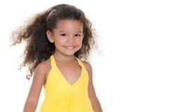 Small hispanic girl wearing a yellow summer dress. Cute small hispanic girl wearing a yellow summer dress isolated on white Stock Photo
