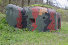 Small historic WWII bunker in camo colours Stock Photos