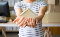 Small home model on woman hand. Home office, business real estate concept. And Family life royalty free stock photo