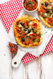 Small homemade vegetable pizza with addition of cherry tomatoes, olives and herbs on a white wooden table Royalty Free Stock Images