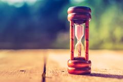 Small hourglass show time is flowing on old wood grunge texture. stock images