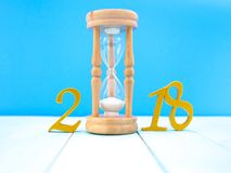 A small hourglass. A small  hourglass on pale blue wooden background Stock Photography