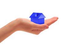 Small house. Female hand which holds a blue small house Royalty Free Stock Photography