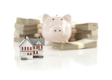 Small House And Piggy Bank With Stacks Money Stock Photos