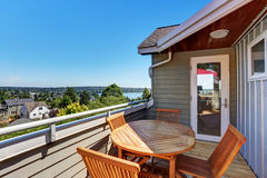 Small house balcony with wooden table set Stock Photos