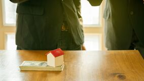 A small house is on a businessman`s dollar and an insurance concept with money