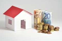 Small house with coins Stock Photos