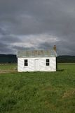 Small house in countryside. Scenic view of small white house in countryside field Royalty Free Stock Images