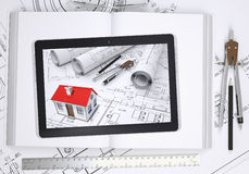 Small house with drawings displayed on tablet Royalty Free Stock Photo