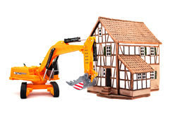 Small house and excavator Royalty Free Stock Images
