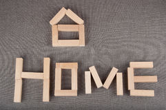 Small house figure and word home made of toy wooden bricks lay on grey background Stock Photos