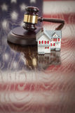 Small House and Gavel on Table with American Flag Reflection Royalty Free Stock Photography