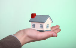 Small house in hand on green background Stock Photography