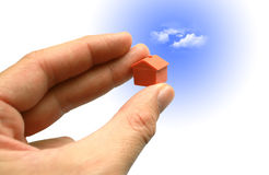 Small house in hand with sky Royalty Free Stock Photography