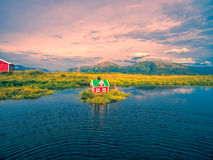 Small house on island. Romantic miniature scandinavian red house on tiny islet royalty free stock images