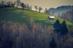 Small house isolated on a hill with some trees in the foreground shot after sunrise against a cloudy sky royalty free stock photo