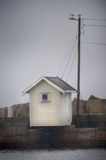 Small house on jetty. White house an a jetty of stone with power lines Royalty Free Stock Photography