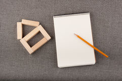 Small house made of small wooden blocks, white notepad and yellow pencil lay on grey fabric Royalty Free Stock Image