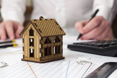 Small house and a man in the background taking notes Royalty Free Stock Image