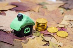 Small house on maple leaves. Autumn rental price concept. Abstract price increase photo stock images