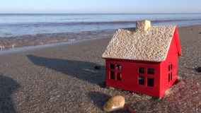 Small house model on ocean beach sand. Small red house model on ocean beach sand
