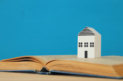 Small house model over open book. selective focus Stock Photography