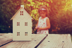 Small house model over wooden table outdoors at garden and kid playing. selective focus . filtered image Stock Image