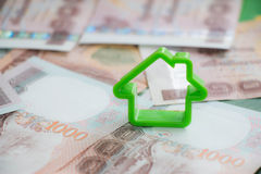 Small house on money Stock Images