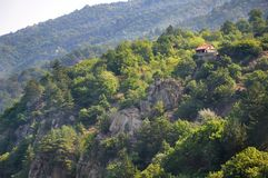 A small house on a mountain slope covered with green vegetation. For your design Stock Photography