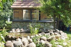 Small house with a pond in the garden stock photos