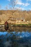Small house on a pond with reflections. Tree reflected on the water at a pond, with a small wooden house on the shore Stock Image