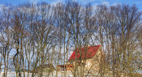 A small house with a red roof on a hill in the forest Royalty Free Stock Photography