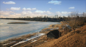 Small house on the shore of a frozen lake Royalty Free Stock Photos