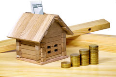 A small house standing at building materials and coins. Credit f Stock Image