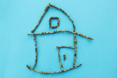 Small house of sticks on a blue background, concept royalty free stock image