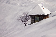 Small house surrounded by snow. Small house on soft hills surrounded by snow Royalty Free Stock Photos