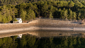 Small house and trees reflected on the dam Royalty Free Stock Image