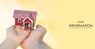 Small house in two hands sun pattern. On nature blurred background Stock Photography