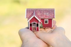 Small house in two hands sun. Nature on blurred background Royalty Free Stock Photos