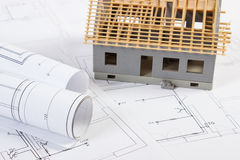 Small house under construction and electrical drawings, concept of building home. Small house under construction and rolls of diagrams on electrical drawings for Stock Image