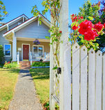 Small house and white fence with roses. Royalty Free Stock Photography