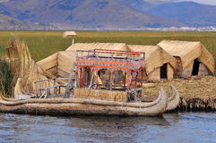 Small houses and boat on Uros islands. Royalty Free Stock Images