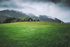 Small houses in a green field with dark sky stock images